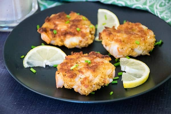 3 shrimp cakes on a black plate with lemon slices and chives