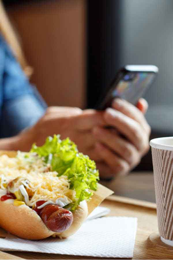 a photo of a hotdog and cup of coffee with person in the background holding a phone (distracted eating)