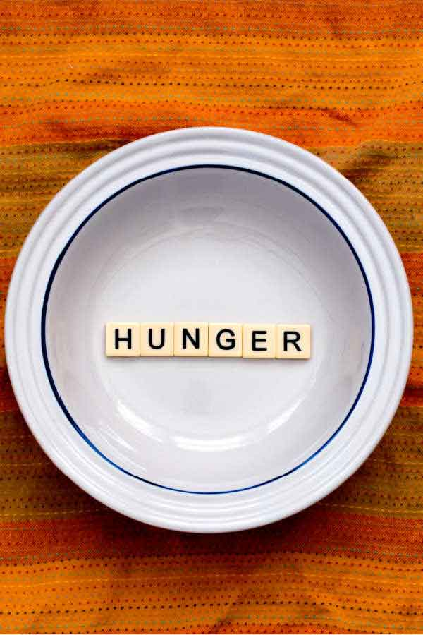 Mindful eating - how hungry are you, a white plate with the words hunger across the plate on an orange towel