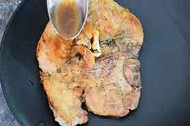 spooning sauce over pork chop