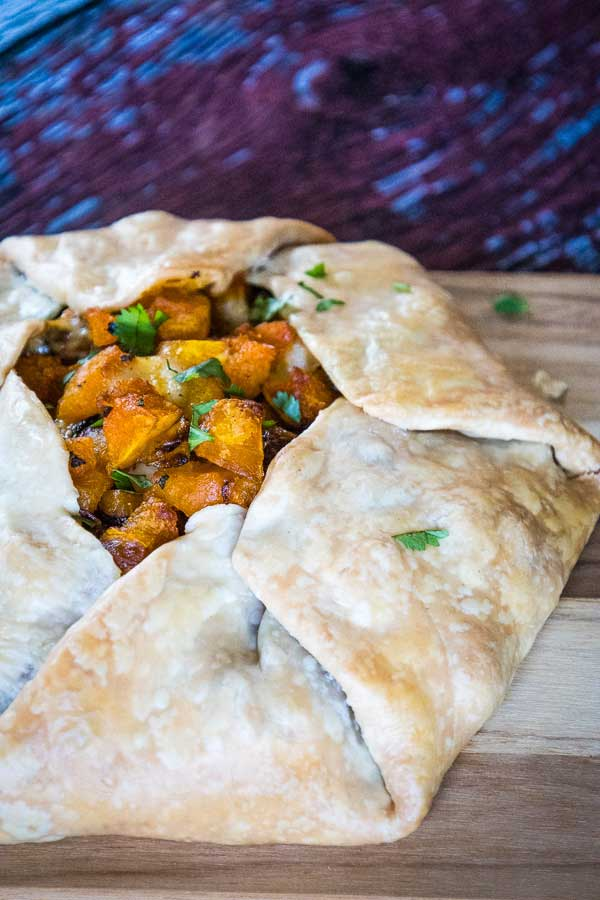 upclose image of baked butternut squash galette on a cutting board