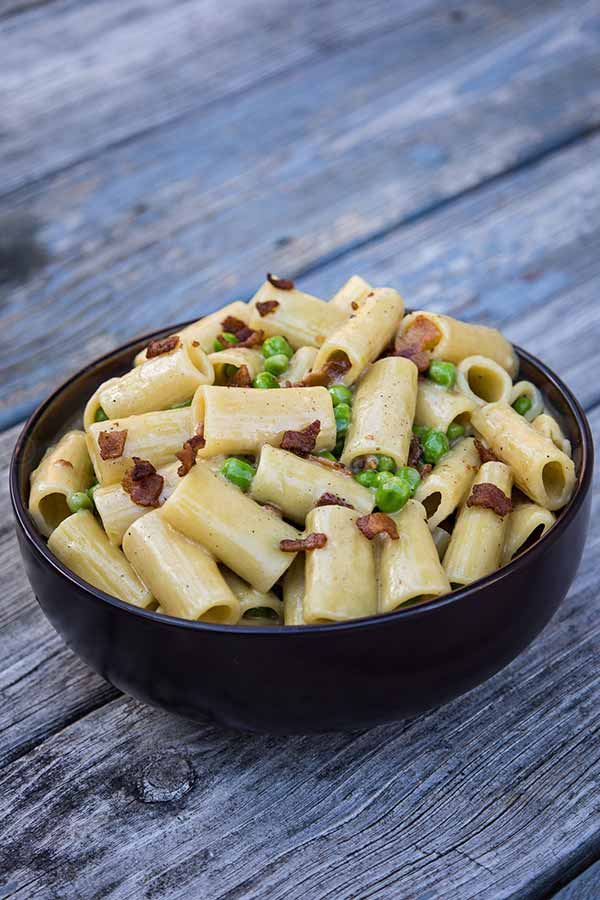 a bowl full of rigatoni pasta with an alfredo sauce, bacon, and peas