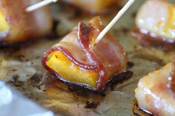 bacon wrapped squash on baking sheet