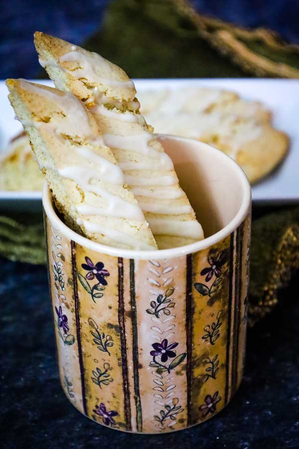 Eggnog biscotti in a floral mug with biscotti on a tray in the background