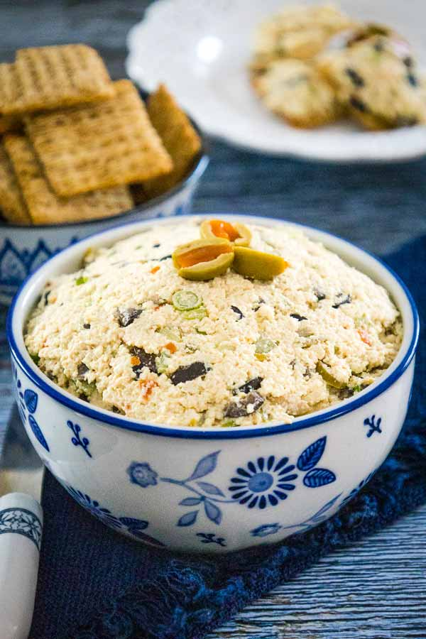 A blue and white bowl full of vegan cheese spread with green olives on top.