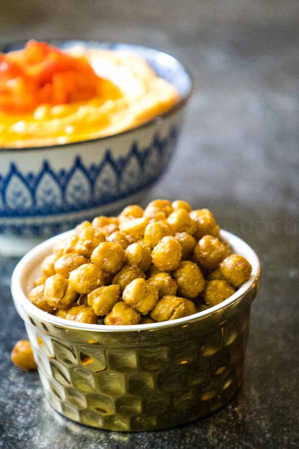 Oven Roasted Chickpeas in a gold serving dish with a bowl of hummus in the background