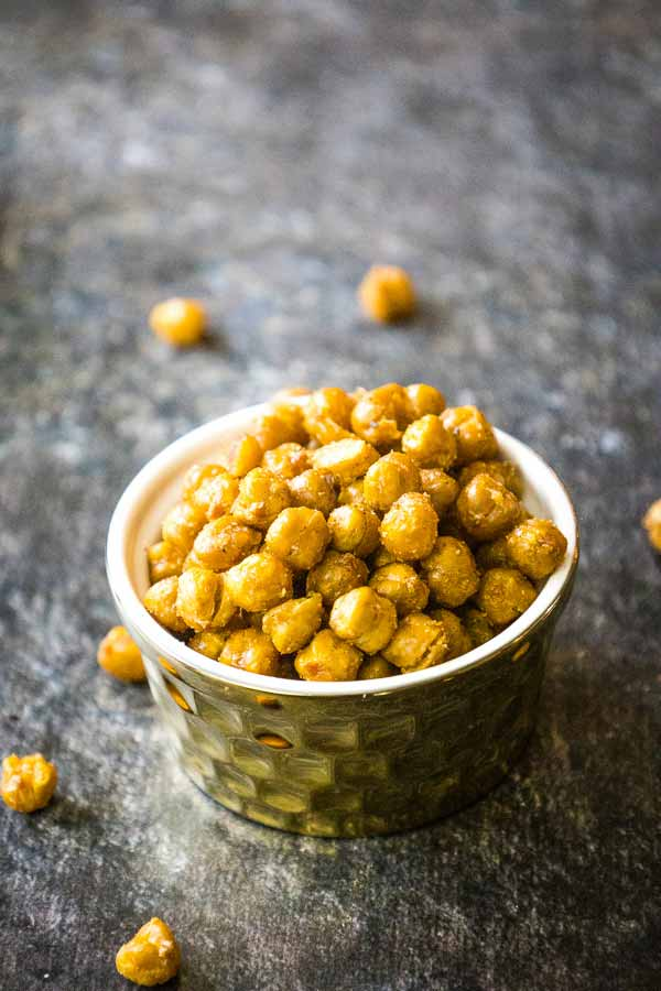 Oven Roasted Chickpeas in a gold serving bowl with a few chickpeas scattered around the dish