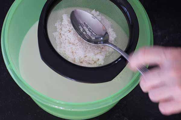 Straining the rice from the soaking liquid.