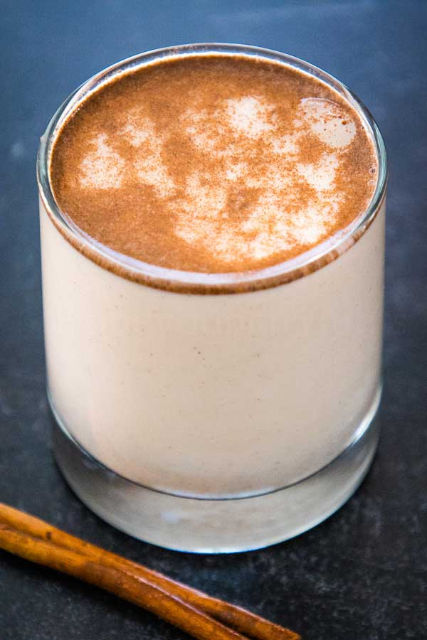 Homemade Horchata in a glass with  cinnamon stick in front of the glass.