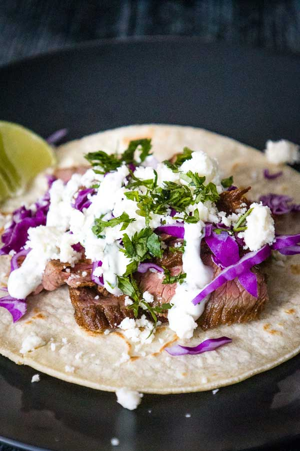 Mexican Street Tacos with Marinated Flank Steak and toppings of red cabbage, cilantro cream, and queso blanco on a plate