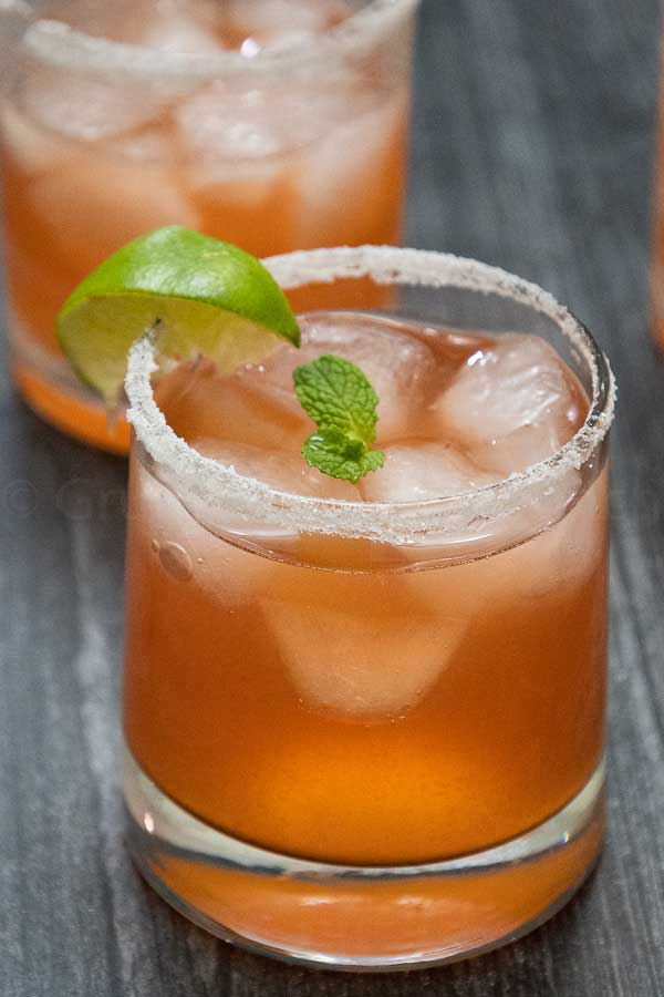 A beverage glass full of strawberry mojito with a sugar rim and lime and mint garnish.