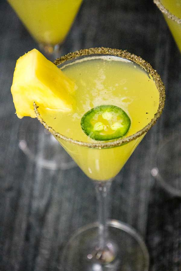 Pineapple Jalapeno Margarita in a sweet black pepper rimmed glass with pineapple and jalapeno garnish