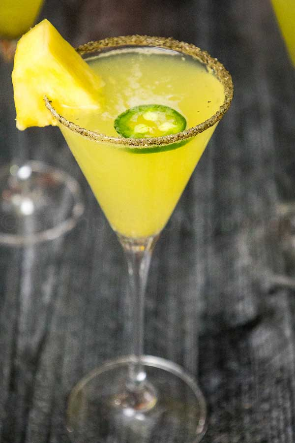 Pineapple Jalapeno Margarita in a glass with a pineapple and jalapeno garnish