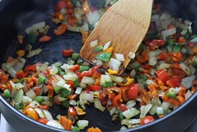 sauteing onions, garlic, and peppers in a skillet.