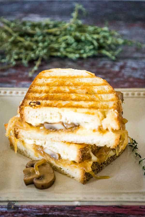 A Caramelized Onion Grilled Cheese Sandwich grilled until golden brown with grill marks on the toasty bread, mushrooms caramelized onions and cheese showing with the sandwich cut in half and stacked on top of each other cut side facing out.