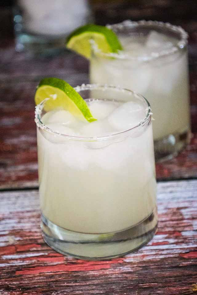 two classic margaritas in a clear drinking glass with salt rim and green lime wedge on top of the glass rim.