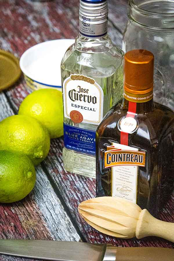 A bottle of Jose Cuervo especial tequila in the center with a bottle of Cointreau to the right and a wooden citrus reamer in front. Three green limes to the left of the tequila bottle and a container of margarita salt in the background