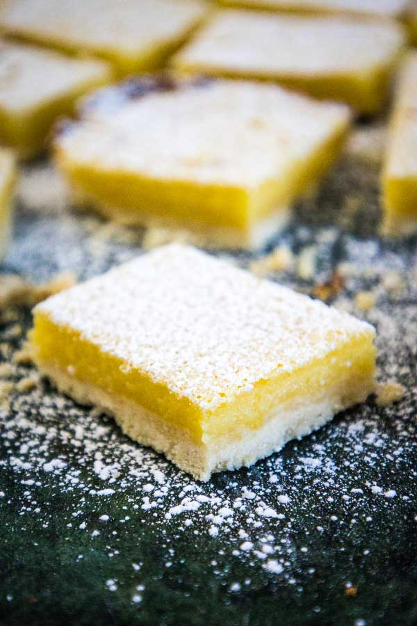 One lemon bar in the foreground with a white shortbread crust and yellow lemon curd filling sprinkled with white confectioner's sugar on top and more lemon bars blurred in the background