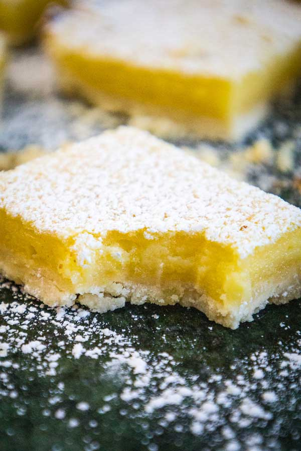 A lemon bar on a green marbled board with one bite taken out of it and another lemon bar blurred in the background.