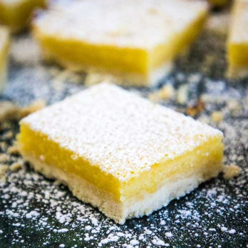 Easy Lemon Bars with a white shortbread crust cut into squares and sprinkled with powdered sugar sitting on a green marbled board with more lemon bars in the background