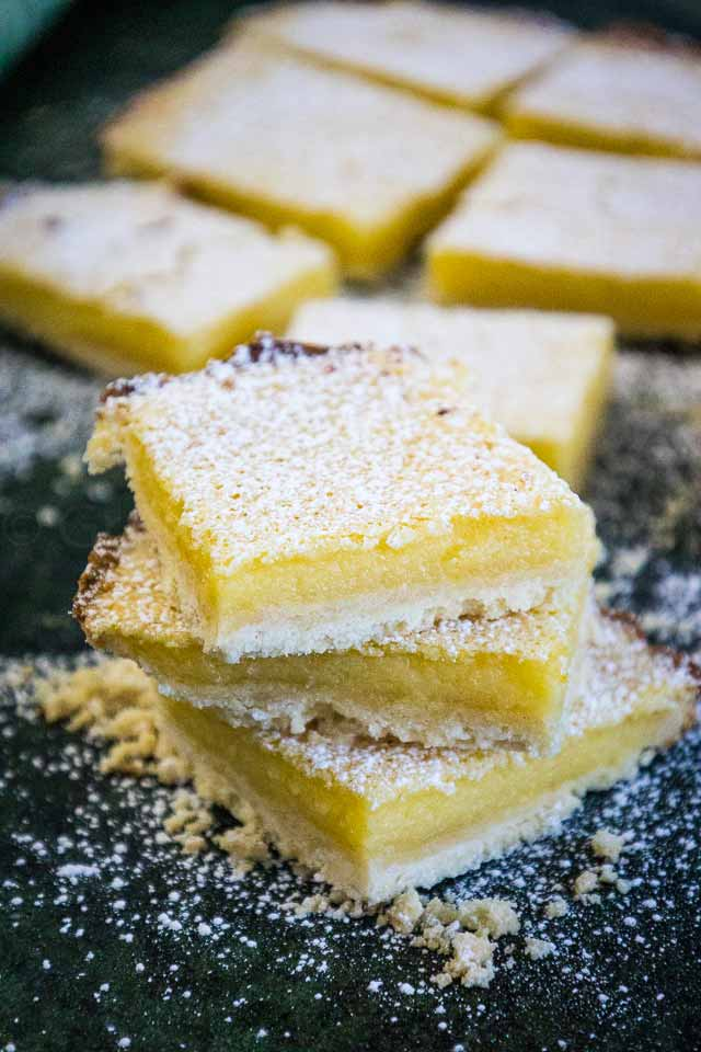 A stack of 3 lemon bars with confectioner's sugar sprinkled over top and more lemon bars in the background.