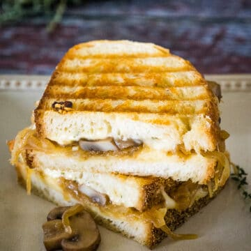 A Mushroom Grilled Cheese Sandwichs with golden grill marks on the bread filled with cheese and caramelized onions.
