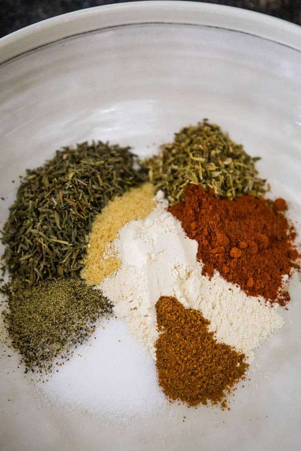 A white bowl with dried thyme, oregano, garlic, onion powder, salt, black pepper, and cayenne spices in a cohesive circle.