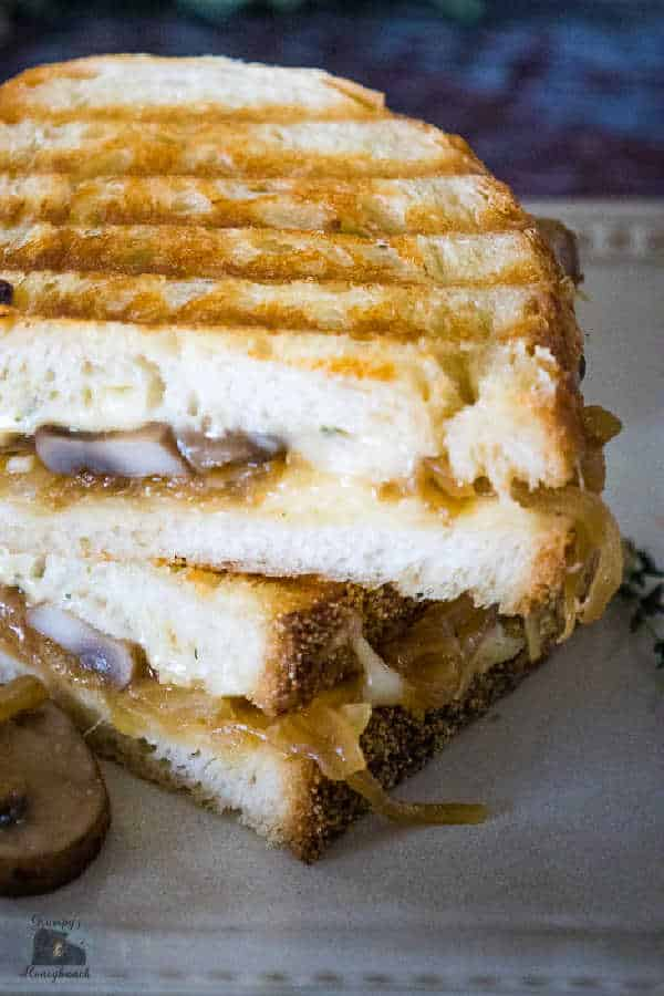 A Caramelized Onion Grilled Cheese Sandwich cut in half and stacked with the mushrooms on the inside of the sandwich visible and one mushroom and caramelized onion on the plate.