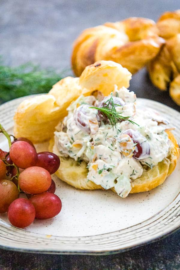 A cream colored plate with chicken salad on top of the bottom half of a golden croissant with a piece of fresh dill on top of the salad and the croissant top behind the sandwich with g apes to the left.