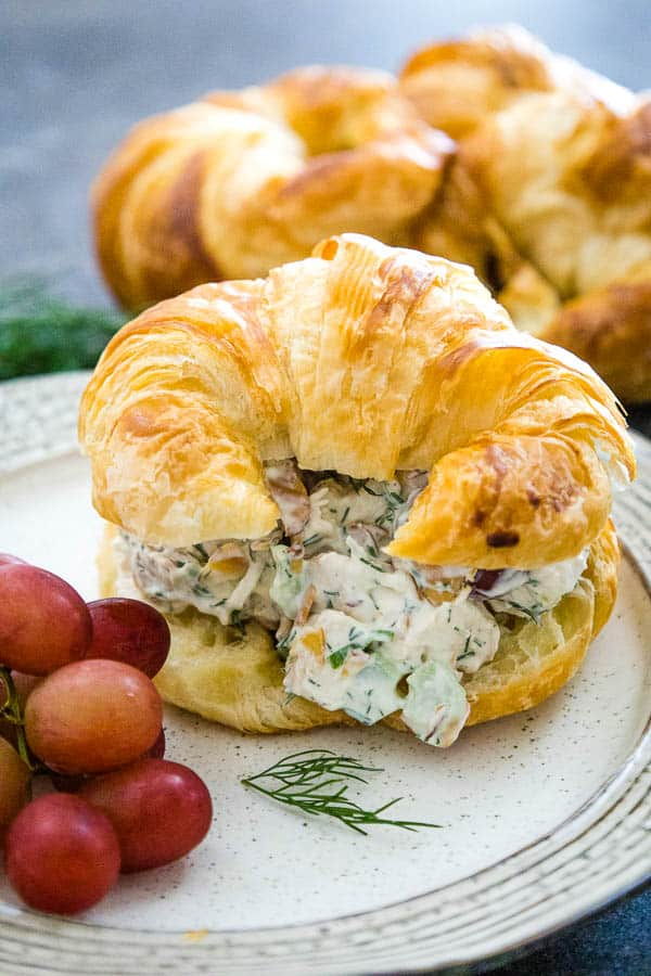 Chicken Salad on a croissant with red grapes next to the sandwichs and a piece of fresh dill in front of the sandwich with croissants blurred in the background.