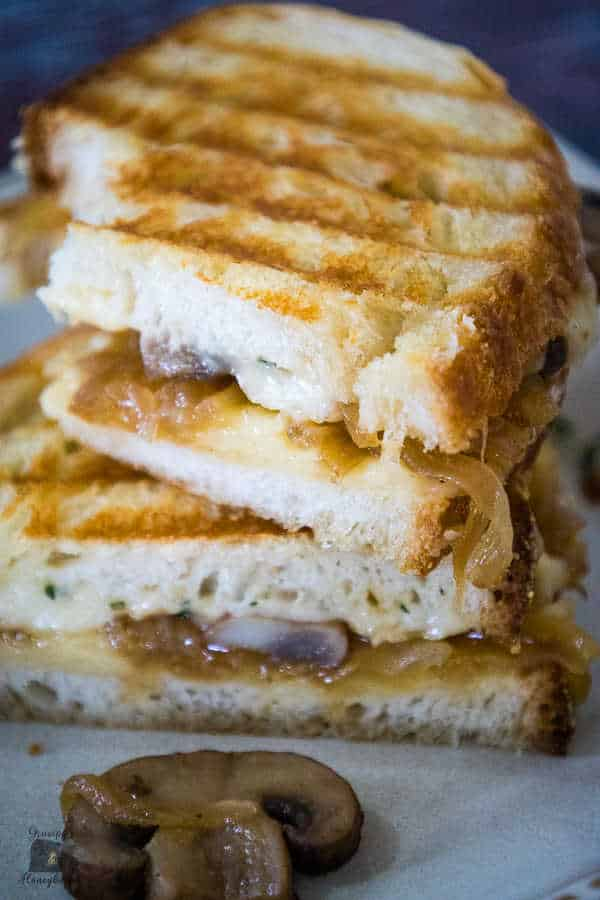 Caramelized Onion Grilled Cheese Sandwich with fried mushrooms grilled until golden with grill marks on the bread cut in half and stacked with one mushroom and caramelized onion on the plate that fell out of the sandwich.
