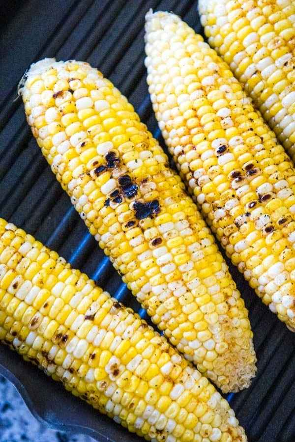 Four ears of corn on a grill pan with charred spots on the grilled corn.