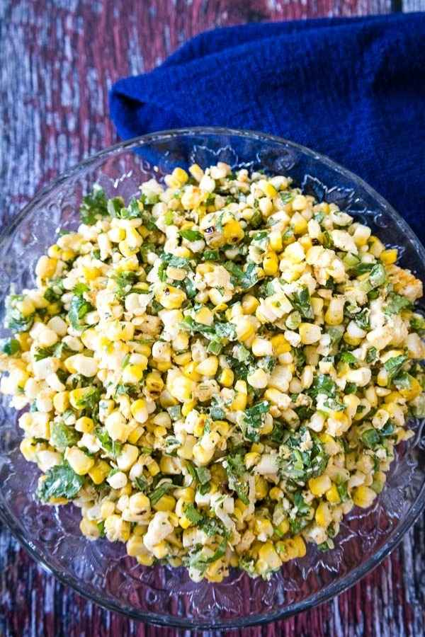 Mexican Street Corn Salad with green jalapeno, cilantro, and scallions in a glass bowl.