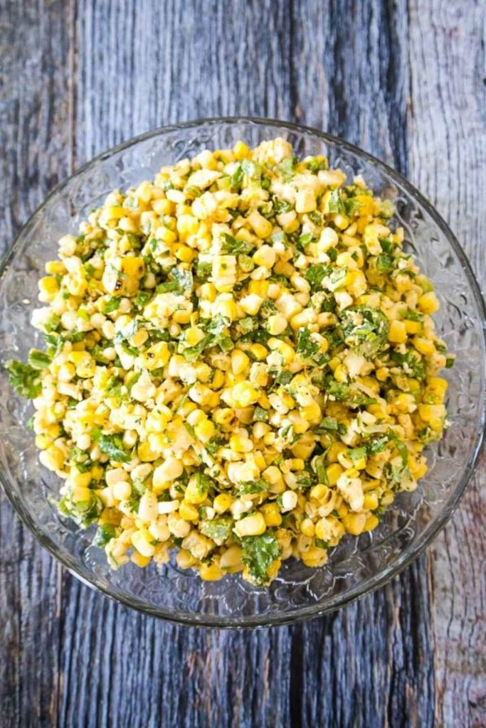 Mexican Street Corn Salad in a glass bowl with yellow grilled corn, green jalapeno, scallions, and cilantro.