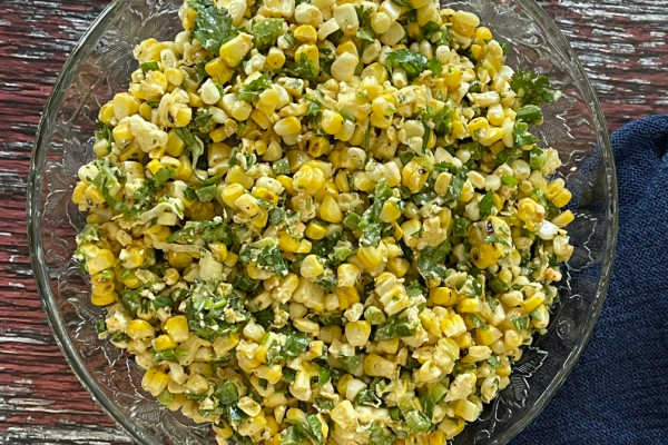 Mexican Street Corn Salad with green jalapeno, cilantro, and scallions in a glass bow