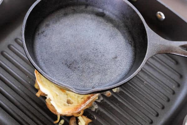 A small cast iron skillet placed on top of the sandwich while it is grilling on the grill pan.