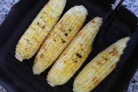 Corn on a grill pan with blistered pieces of corn showing on top.