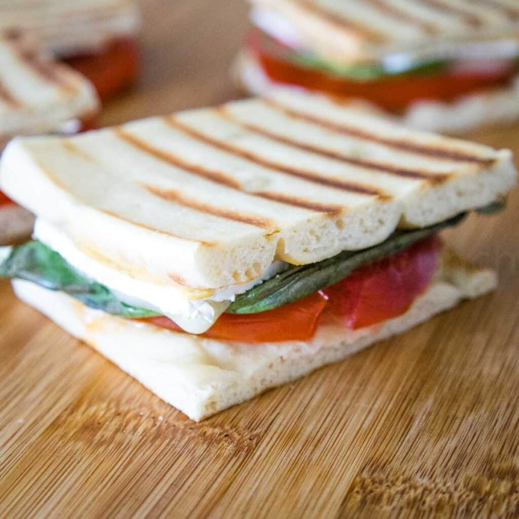 Fully assembled brie tomato sandwich with a layer of flatbread cheese, tomato, basil, and more cheese
