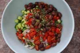 A blue mixing bowl with cucumbers, cherry tomatoes, kalamata olives, red onion, brown lentils, and fresh chopped oregano ready to be tossed.