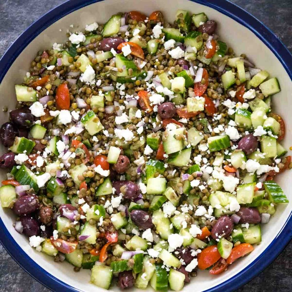 Overhead view of a fully assembled lentil salad made with brown lentils, black kalamata olives, red grape tomatoes, diced cucumbers and red onions tossed with feta cheese in a cream ceramic serving dish with a blue rim.