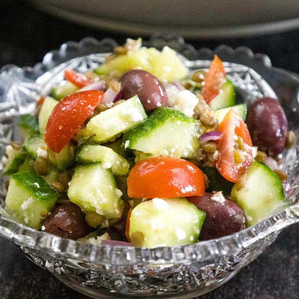 Crystal glass bowl with a single serving of lentil salad made with diced cucumbers, grape tomatoes, black olives, feta cheese in a lemon dressing.