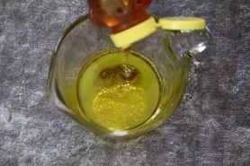 adding honey to the mixing bowl for the lemon vinaigrette.