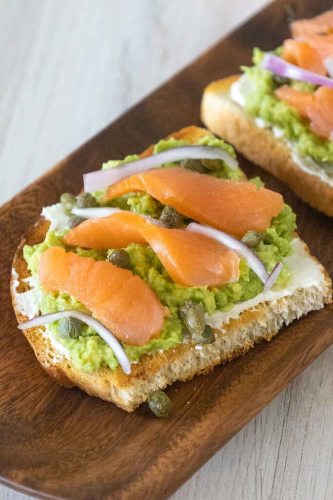Avocado Toast topped with smoked salmon slices, thinly sliced red onion and capers on an aicia wood tray