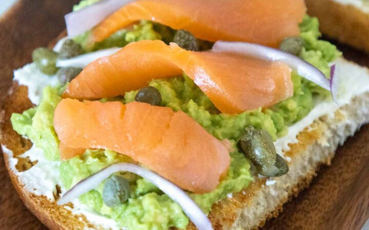 A slice of toast with a layered spread of cream cheese, mashed avocado, smoked salmon pieces, capers, and red onions on a brown acaia tray