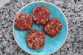 4 raw burger patties on a blue plate