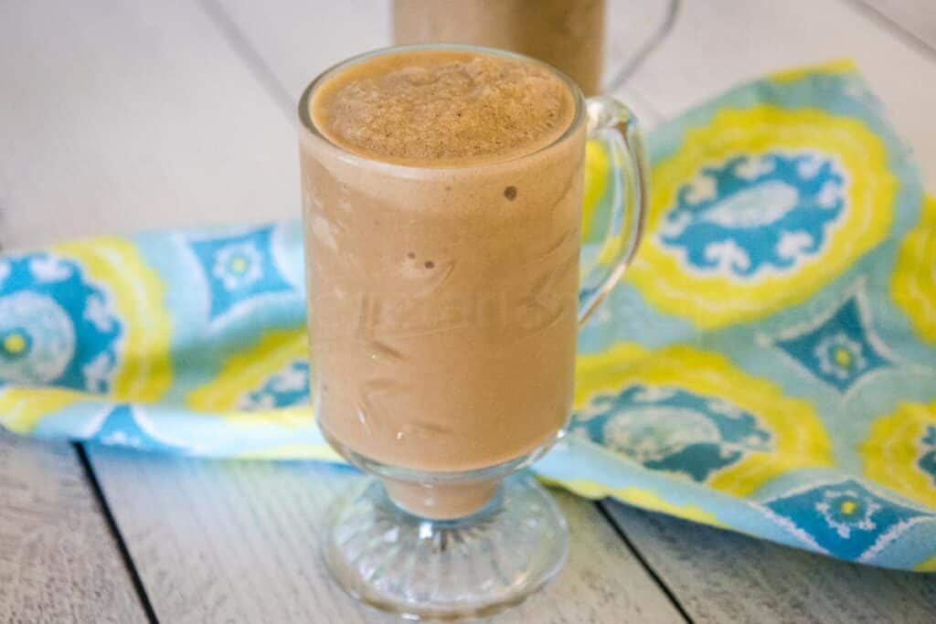 Banana Coffee Smoothie in a clear glass footed mug with a blue and yellow napkin the background.