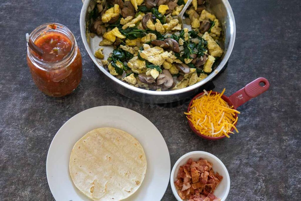 From top going clockwise in a circle, stainless steel skillet with scrambled eggs, mushroom, and spinach mixture, a red measuring cup with yellow shredded cheese, a small white prep bowl with chopped cooked babon, a white plate with toasted corn tortillas, and a pint jar of salsa with a spoon in the jar.