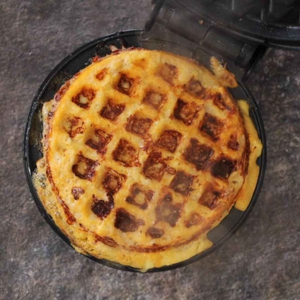 Golden brown chaffle in the mini waffle iron.