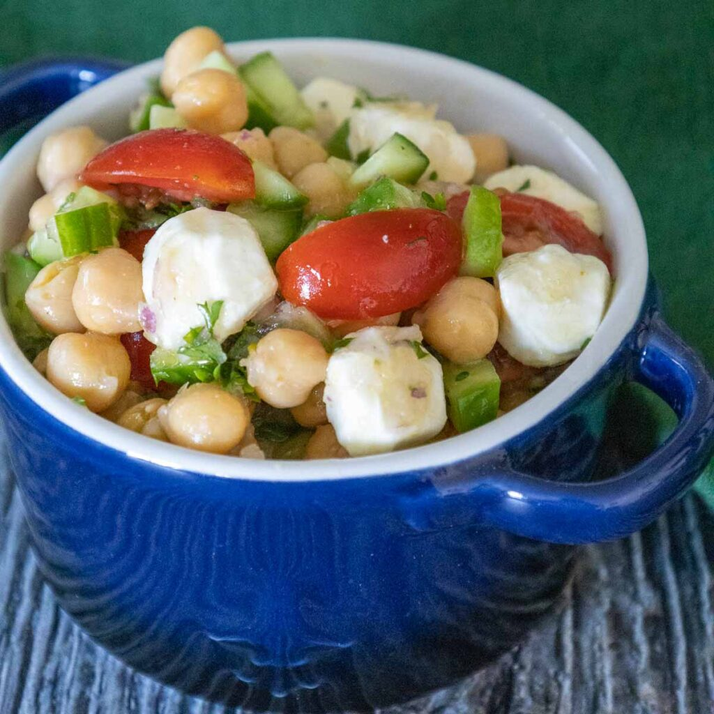 A blue bowl full of Mediterranean Chickpea Salad with chickpeas, diced cucumbers, chopped red tomatoes, red onion, and fresh mozzarella balls.