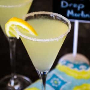 Up close image of a lemon martini with a sugar rim, lemon wheel garnish and a dark blue, light blue, white, and yellow patterned napkin blurred in the background.